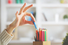 Girl taking blue pencil. Close up of girl`s hand taking blue pencil out of holder on blurry shelf background Royalty Free Stock Photos