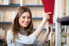 Girl taking a book in a library Stock Photo