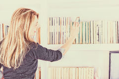 Girl taking a book from top shelf Royalty Free Stock Photo