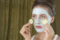 Girl taking care of her complexion layering moisturizer. She holds a cucumber. Young woman taking care of her complexion layering moisturizer Stock Images