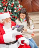 Girl Taking Christmas Gift From Santa Claus Royalty Free Stock Images