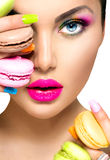 Girl taking colorful macaroons Stock Photography