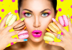 Girl taking colorful macaroons Stock Images