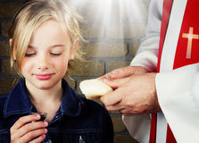 Girl taking Communion. A little girl taking communion from her pastor Royalty Free Stock Photo