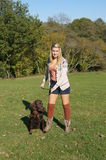 Girl Taking Dog for a Walk. Pretty Girl taking her flat-coated retriever dog for a walk Stock Image