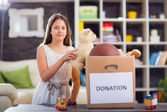 Girl taking donation box full with stuff for donate Stock Photography