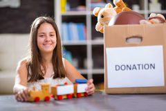 Girl taking donation box full with stuff for donate Royalty Free Stock Image