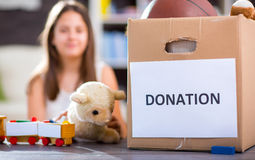 Girl taking donation box full with stuff for donate Stock Images