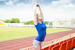Girl taking exercise outdoors. Athletic girl  doing some stretching exercises outdoors Royalty Free Stock Photography