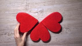 Girl taking four red hearts from a wooden table, top view. Care, love, Valentine's day concepts. 4K video. Girl taking four red hearts from a wooden table, top stock video