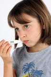 Girl taking her temperature Royalty Free Stock Image