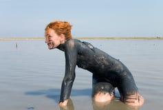 Girl taking mud bath outdoor Royalty Free Stock Photo