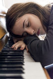 Girl taking a nap after practice playing the piano Royalty Free Stock Photo