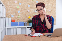 Girl taking notes during phone conversation. Girl in office in casual clothes is talking on her cell phone and making notes with pencil. Book shelves with Royalty Free Stock Image