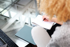 Girl taking notes while sitting on the sofa Stock Photo