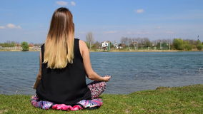 Girl taking off butterfly wings and continuing whit meditation in lotus position next to the calm water. A girl taking off butterfly wings and continuing whit stock footage