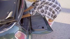 Girl taking out her roller skates from trunk stock footage