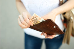 Girl is taking out money from wallet Stock Image
