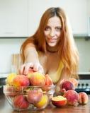 Girl taking peaches at home kitchen Royalty Free Stock Photos