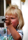 Girl taking photo. Toddler girl with blond hair taking a photo with a digital camera stock photos