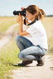 Girl taking photo with camera. Young girl taking photo with camera against field Stock Photography
