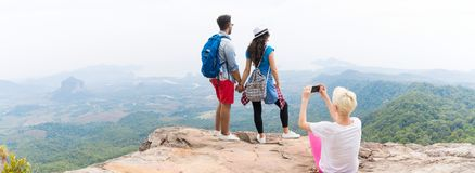 Girl Taking Photo Of Couple With Backpacks Posing Over Mountain Landscape On Cell Smart Phone Panorama, Trekking Young Royalty Free Stock Image