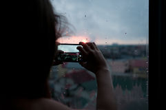 Girl taking photo of evening city Royalty Free Stock Image