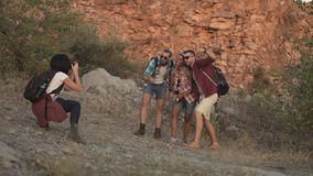 Girl taking photo of friends while traveling. Mixed racial friends taking shot of three friends posing with backpacks while traveling together stock video footage