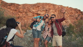Girl taking photo of friends while traveling. Mixed racial friends taking shot of three friends posing with backpacks while traveling together. Slow motion stock footage