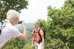 Girl Taking Photo Of Guy With Backpack Posing Over Mountain Landscape On Cell Smart Phone, Trekking Young Man And Woman Royalty Free Stock Image
