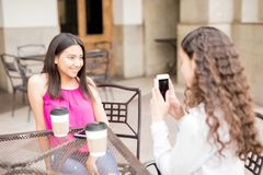 Free Girl Taking Photo Of Friend At Cafe Royalty Free Stock Photography - 116975057