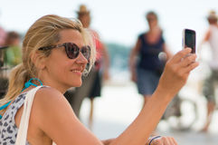 Girl taking photo with phone Stock Image