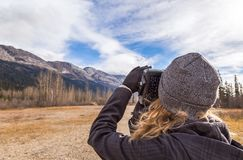 Girl taking photo of the Rocky Mountains royalty free stock images