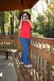 Girl taking photograph Stock Image