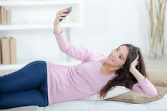 Girl taking photograph herself with cellphone Royalty Free Stock Photo