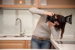 Girl taking a photograph in kitchen interior Stock Images