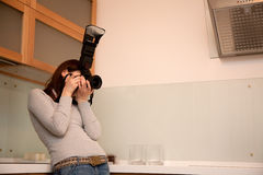 Girl taking a photograph in kitchen interior Stock Photography