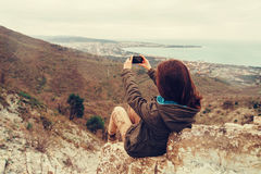 Girl taking photographs landscape with phone Stock Photography