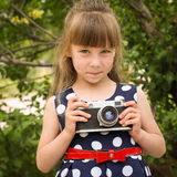 Girl taking photographs with retro camera.  Stock Photos