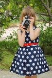 Girl taking photographs with retro camera.  Royalty Free Stock Image