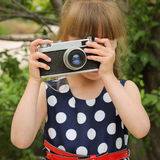 Girl taking photographs with retro camera.  Royalty Free Stock Photos