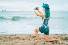 Girl taking photographs of sea Stock Photos