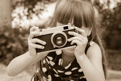 Girl taking photographs with vintage camera. Stock Image