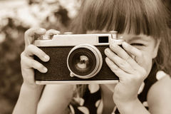 Girl taking photographs with vintage camera. Royalty Free Stock Image