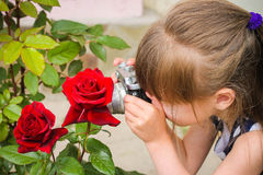 Girl taking photographs with vintage camera. Royalty Free Stock Images
