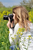 Girl taking photos. In rapeseed field Stock Images