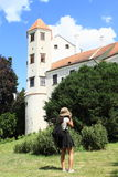 Girl taking photos of castle in Telc Stock Photo