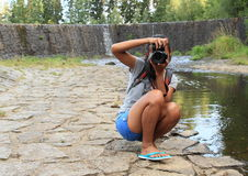 Girl taking photos in front of dam of pond Stock Image