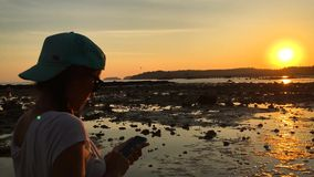 Girl Taking Picture of Amazing Sunset with her Smartphone on the beach. HD Slow Motion. Thailand. stock footage