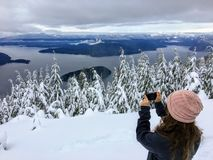 A girl taking a picture atop Cypress Mountain overlooking the ocean below. In the distance hikers and snowshoers can see Howe Sound, Sunshine Coast, Bowen and stock photo